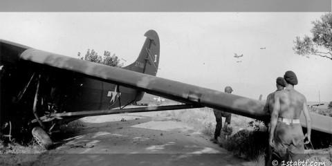 Des parachutistes britanniques del a 2nd Independent Para Brigade observent des planeurs en descente à côté d'un planeur Waco.