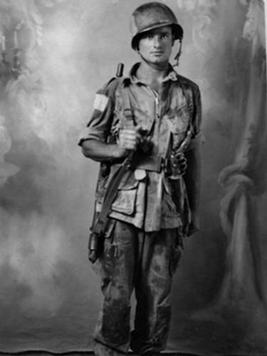 Trooper du 504th PIR en Sicile. Le camouflage de son casque, en losange, le montre comme appartenant au 2nd Battalion, la tenue est également camouflé en Olive Drab et noir. Des leg ties (sangle de jambes) ont étaient cousus pour maintenir les poches cargo du pantalon. Les poches inferieures de la veste, les poches cargo et les genoux du pantalon ont étaient renforcé avec de la toile de bâche. Ce serait le premier type de tenue renforcé, comme vu en Normandie, mais fait beaucoup moins soigneusement et à la hâte.