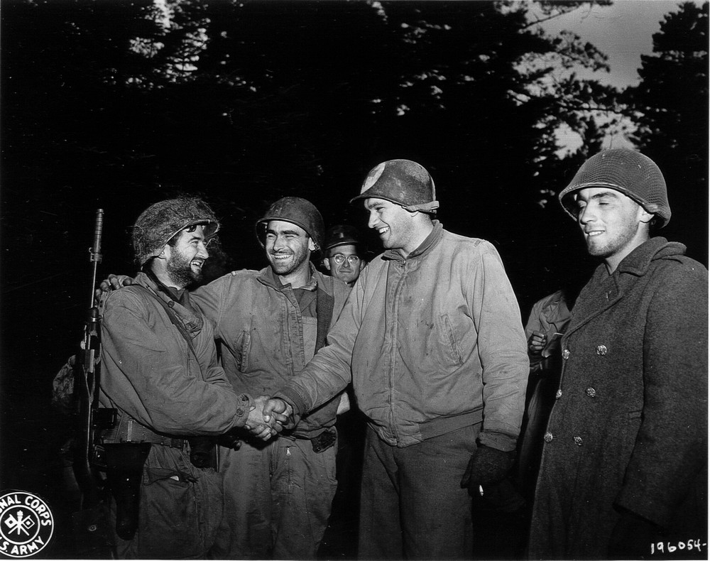 "Courtesy photo Lt. Marty Higgins (left with beard), commander of the ""Lost Battalion,"" part of the 36th I.D. of Texas (known as T-patchers) in the Vosges Mountains, France, shakes hands with fellow G.I.s after the 442nd Regimental Combat Team breaks through German lines to rescue the battalion which had been cut off from supplies and allies. The 442nd was comprised primarily of Japanese Amercan soldiers."