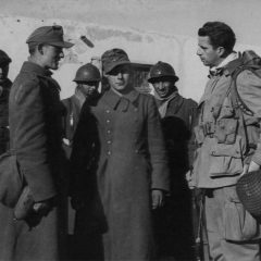 Maj. William P. Yarborough with French soldiers talking to Germans POW. Yarborough is wearing the french fourragère of the 3rd Zouave.